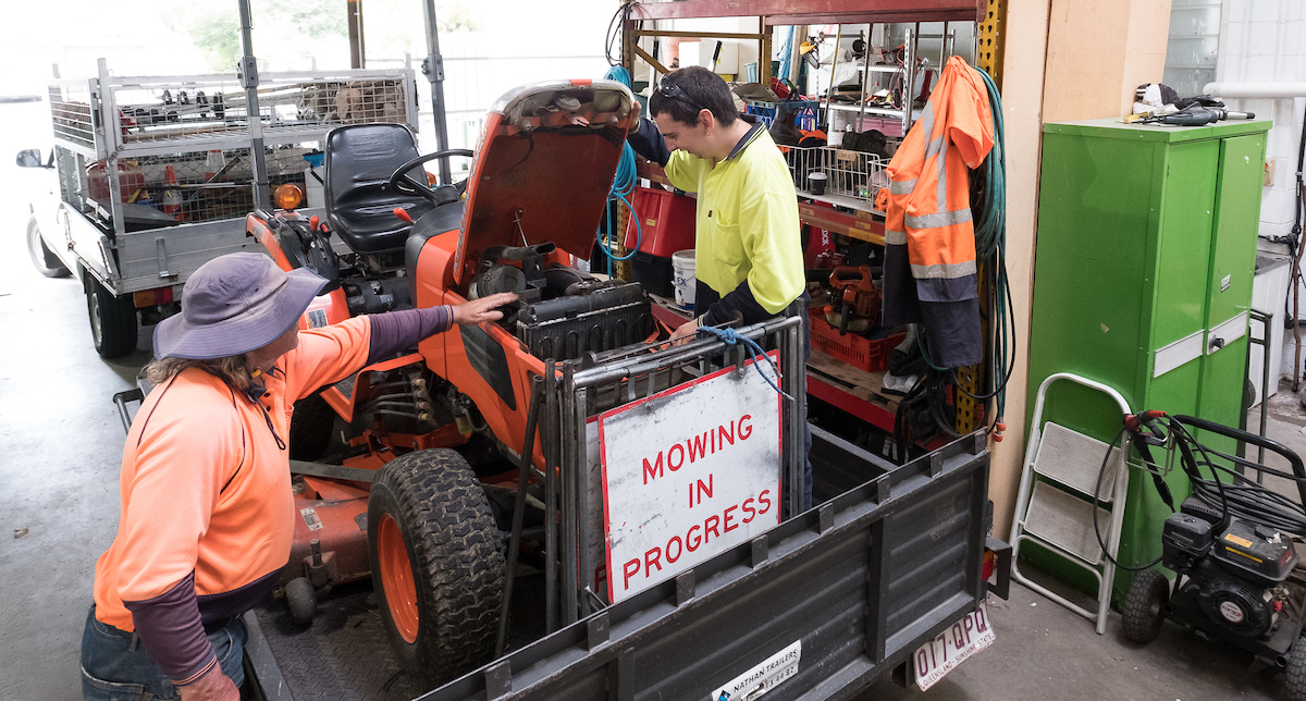 Mowing NCEC workers checking mower engine. 2 people wearing orange and yellow high vis shirts.
