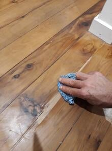 Using a sealant to plug a cavity in the old wooden floor boards