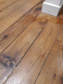 A cavity in the old wooden floor boards