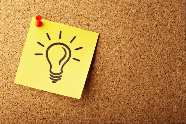 A cork board with a yellow post it note pinned to it. Drawn on the post it note is a lightbulb